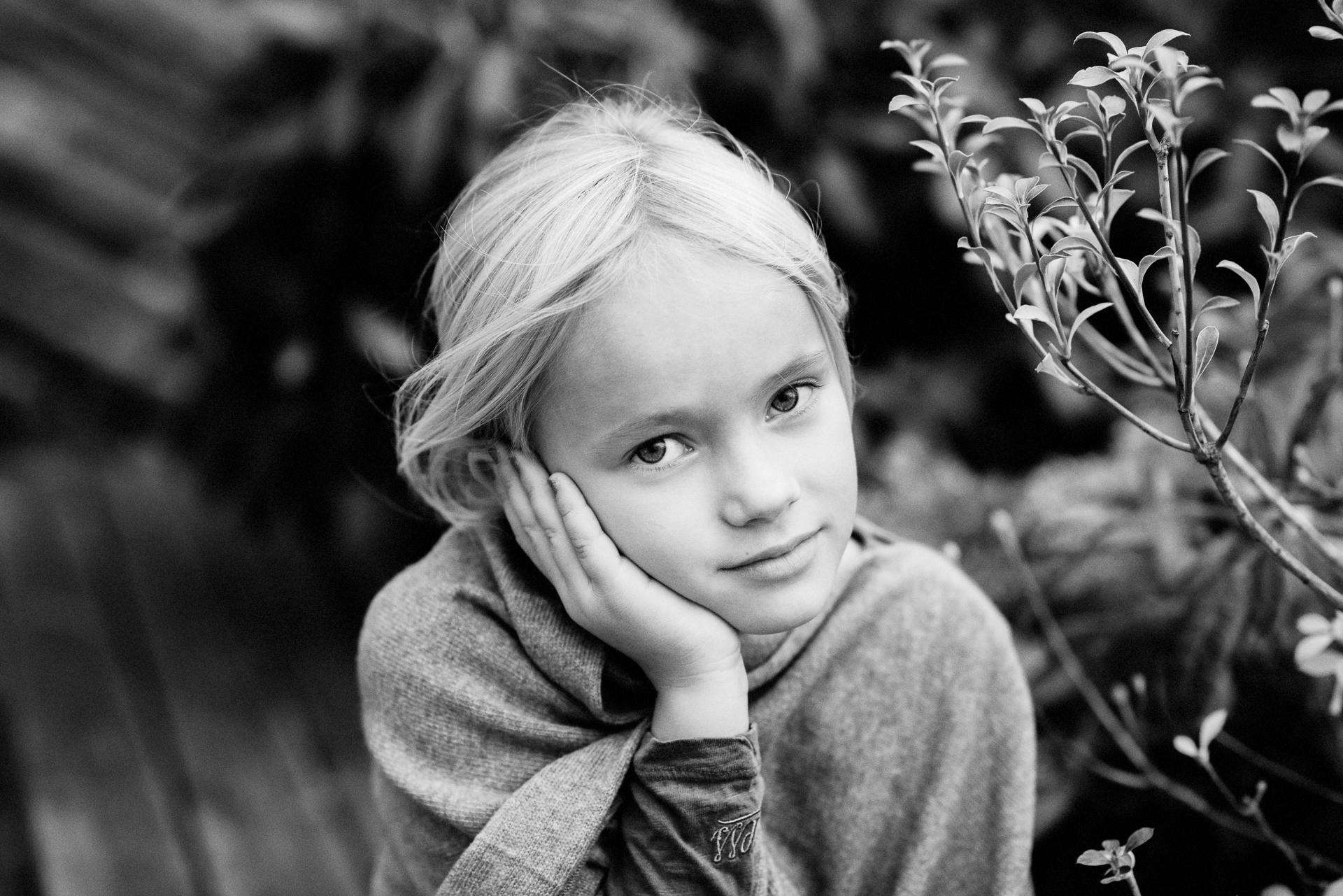 Portrett av jente utendørs som hviler hodet sitt i hånden