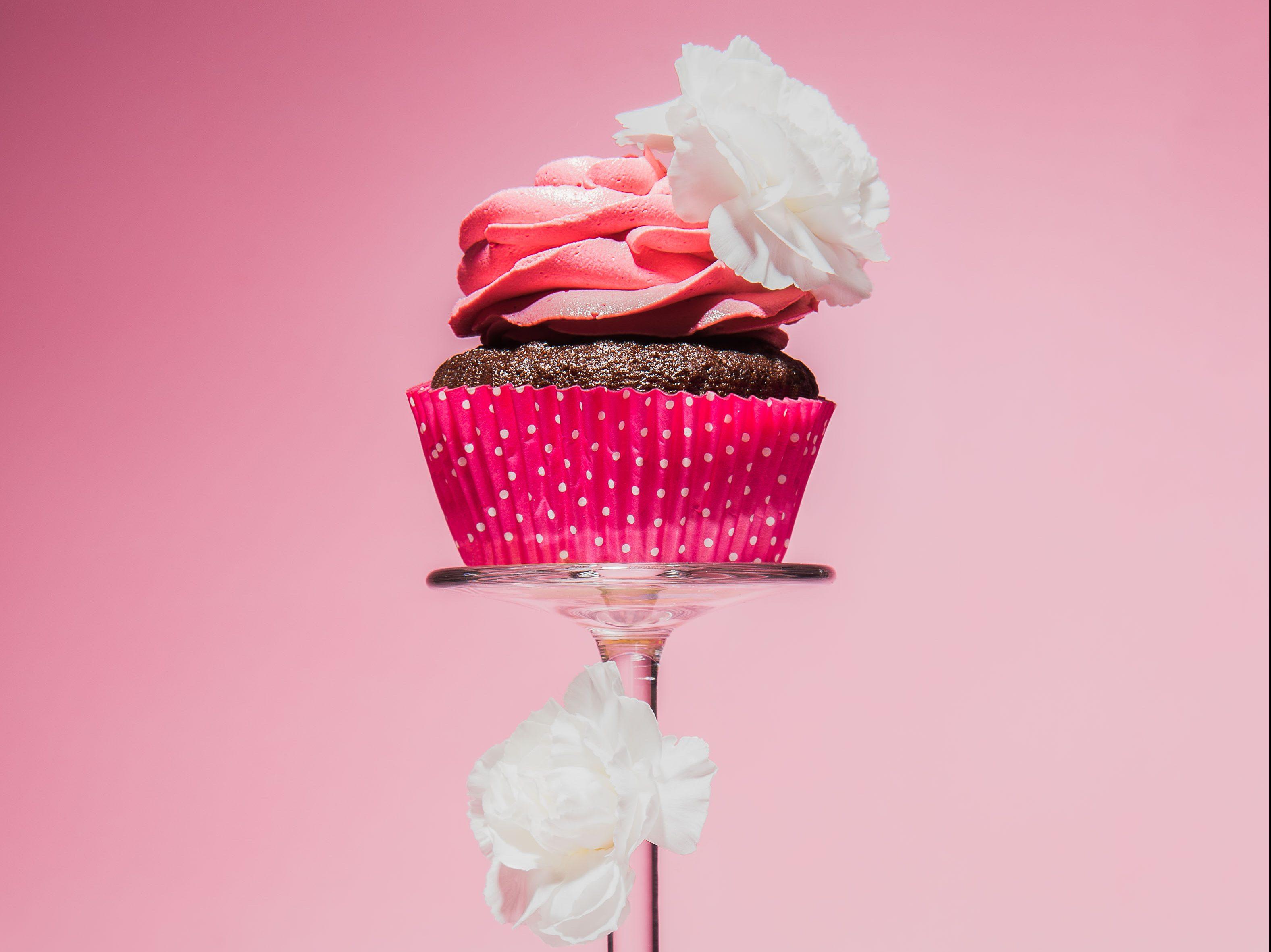 Rosa cupcake på stetten til et vinglass