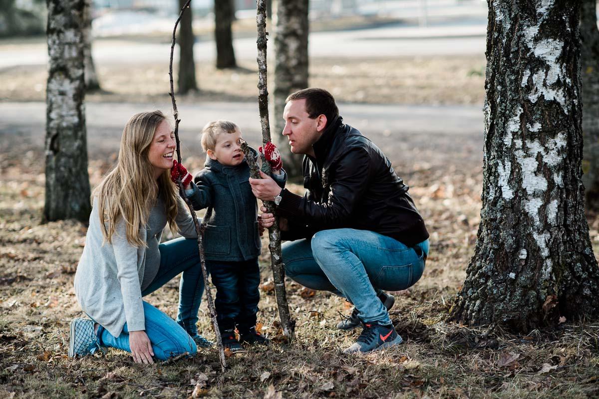 En familie på tre stykker som leker i skogen mens barnet viser frem hva han har funnet